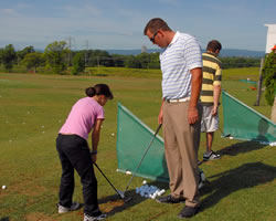 youth golf participant with coach