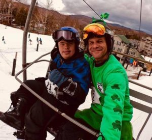 STRIDE Adaptive Sports Program participants Colin and Kevin ride the ski lift at Jiminy Peak.