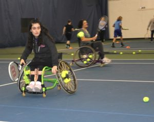 A wheelchair player in the STRIDE tennis program prepares to hit the ball.